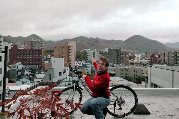My bicycle and me on my host's roof and Sapporo's ski-jump in the background